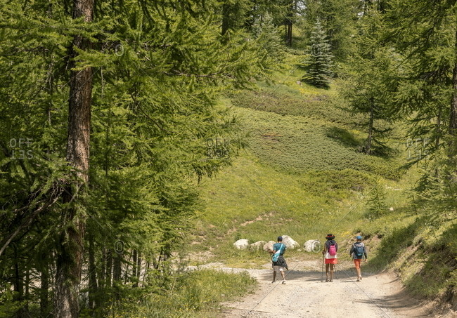 Montgenevre, France - July 18, 2019: Three people hiking from Montgenevre to Brianzoni in the French Alps