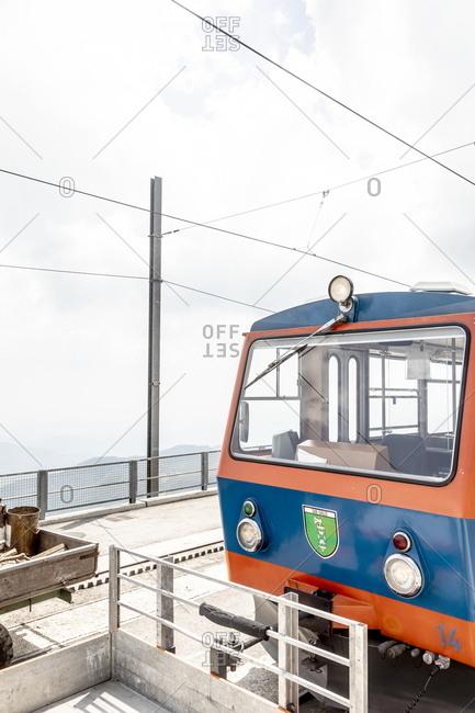 Ticino, Switzerland - June 7, 2019: A blue and orange mountain train traveling from Capolago to Mt. Gneroso