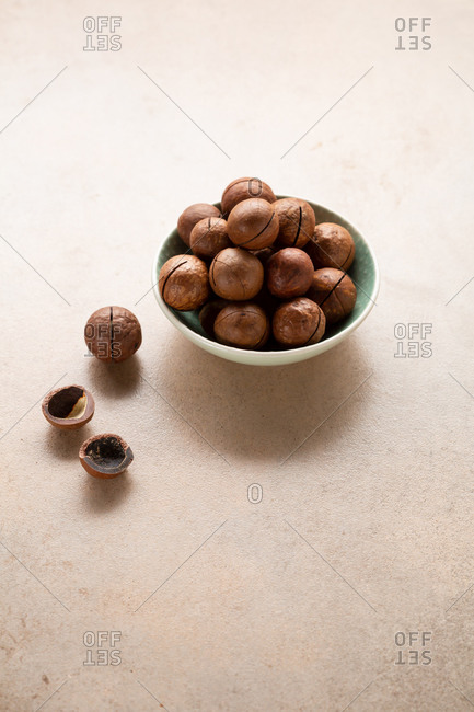 Macadamia nuts in a bowl on light background