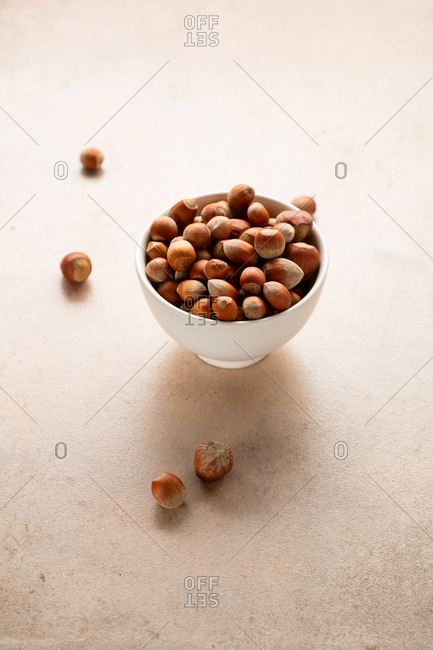 Hazelnuts in a bowl on stone surface