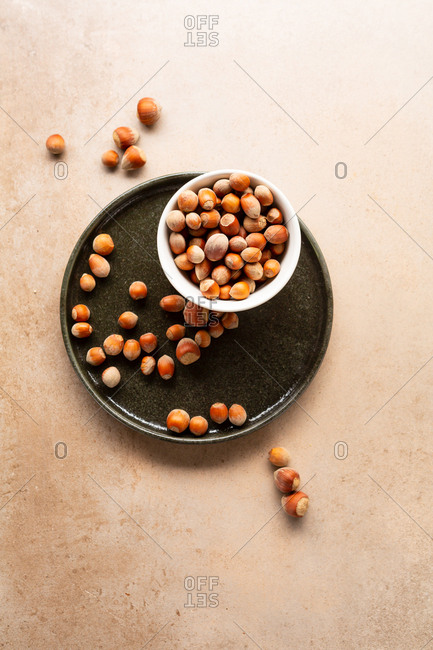 Overhead view of hazelnuts in a bowl on a tray