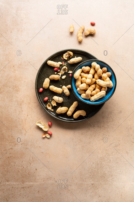 Peanuts in a bowl and on a tray on light surface