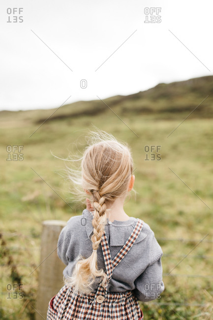Little blonde girl looking out at countryside in Northern Ireland