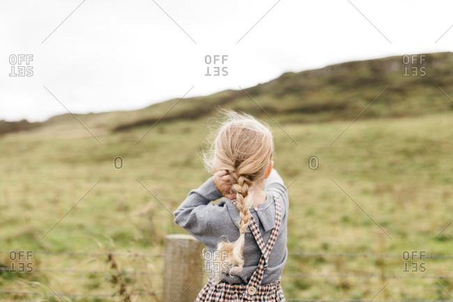 Rear view of a little blonde girl looking out at countryside in Northern Ireland