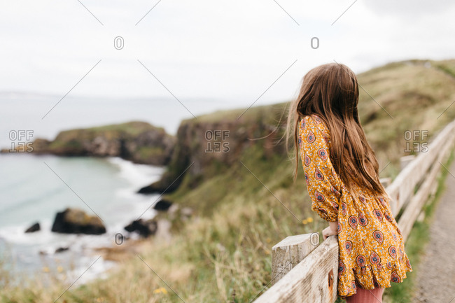 Little girl looking out at the ocean in Northern Ireland