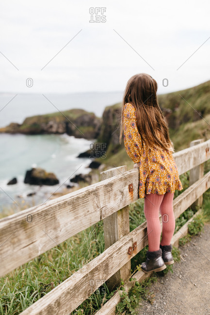 Little girl standing on fence looking out at the ocean in Northern Ireland