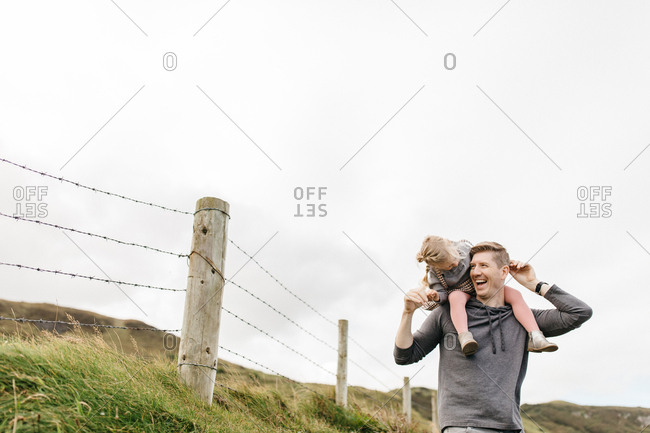 Father carrying daughter on shoulders in rural Northern Ireland