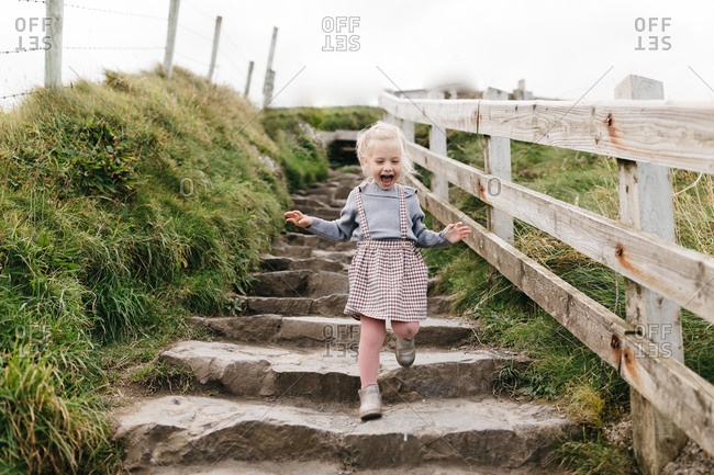 Little blonde girl walking down steps at the National Trust Carrick-a-Rede rope bridge in Northern Ireland