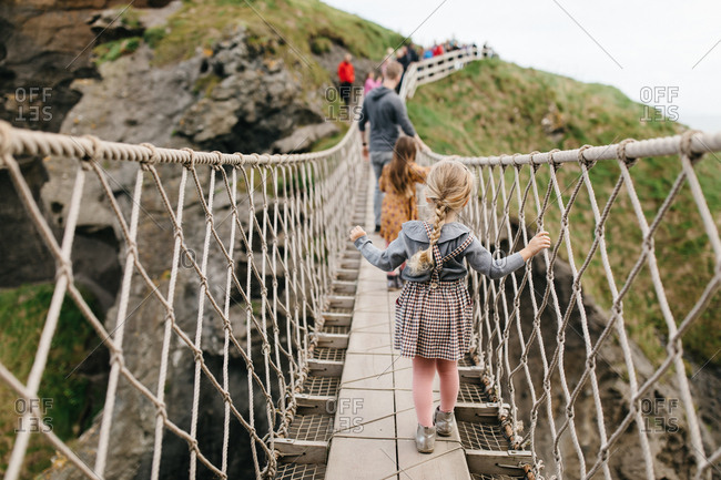 Family crossing the National Trust Carrick-a-Rede rope bridge in Northern Ireland