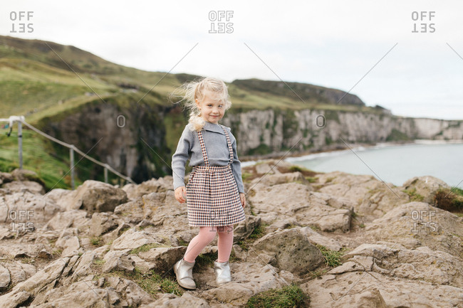 Happy blonde girl standing on cliff at the National Trust Carrick-a-Rede rope bridge in Northern Ireland