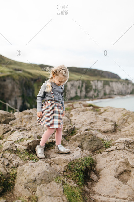 Little blonde girl standing on cliff at the National Trust Carrick-a-Rede rope bridge in Northern Ireland