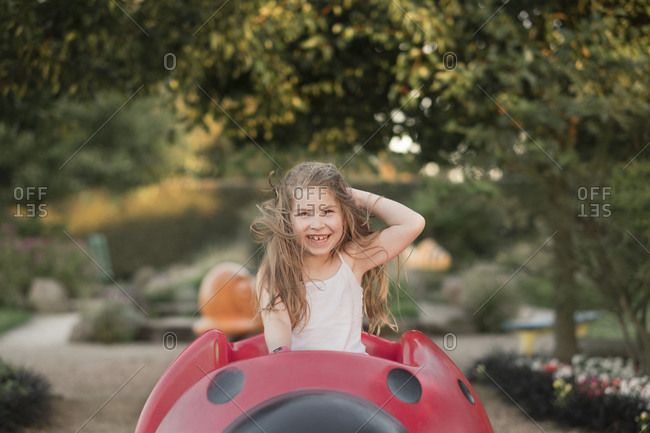 Young girl with messy hair playing on playground equipment