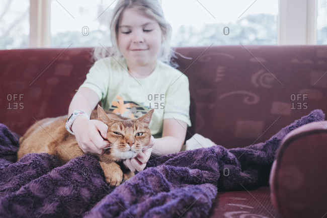 Young girl patting her cat indoors sitting on a sofa
