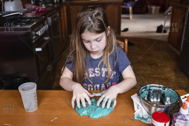 Young girl mixing homemade slime