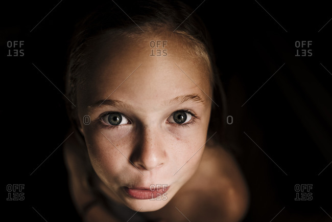 Portrait of little girl with wet hair in low light and dark background