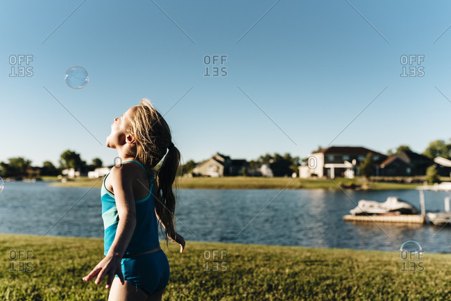 Girl wearing swimsuit near water tries to catch a bubble with mouth