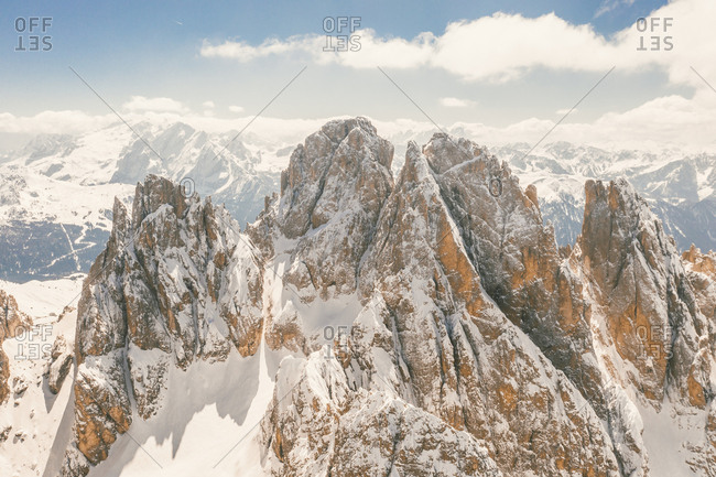 Aerial shot of mountain range under blue sky with clouds