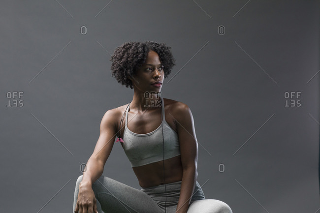 Thoughtful woman looking away while wearing sports clothing against wall in gym