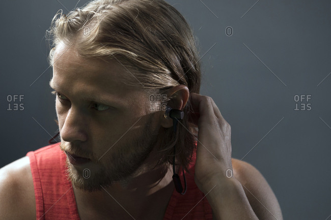 Serious man adjusting hair while listening music in gym against wall