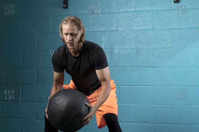 Man using medicine ball while exercising against wall in gym