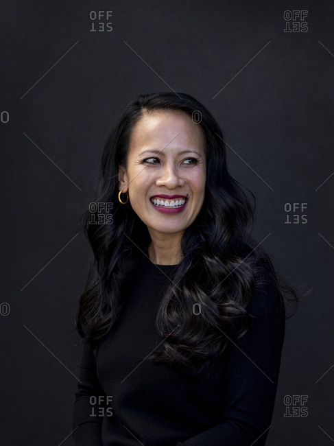Asian female wearing black posing by black background smiling