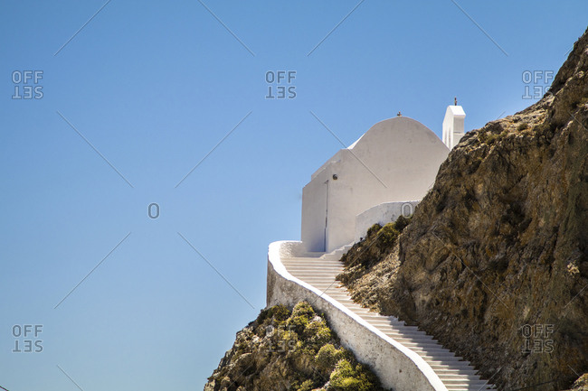 Low angle view of church on mountain against clear blue sky