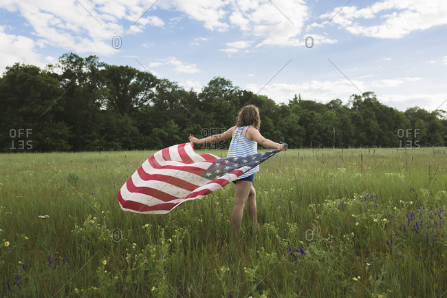 Rear view of girl holding American Flag while walking on grassy field