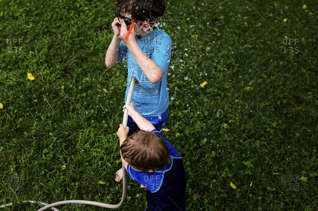High angle view of brothers playing with garden hose in yard