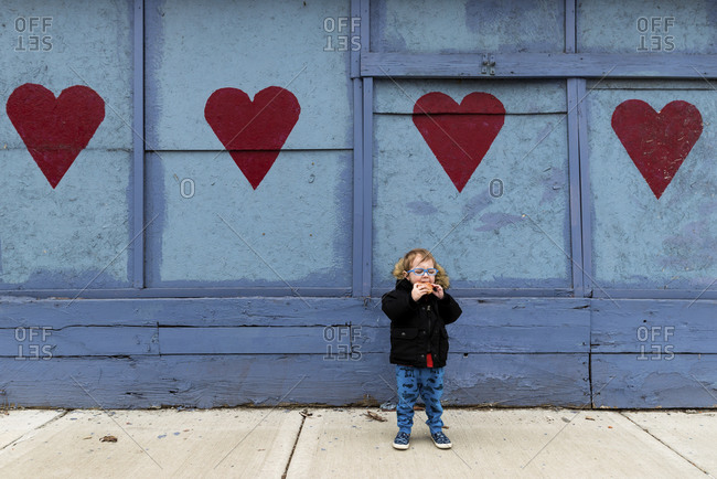 Full length of boy eating food while standing against heart drawn wall on footpath
