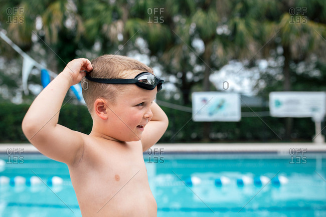 Side view of boy wearing swimming goggles while standing by pool