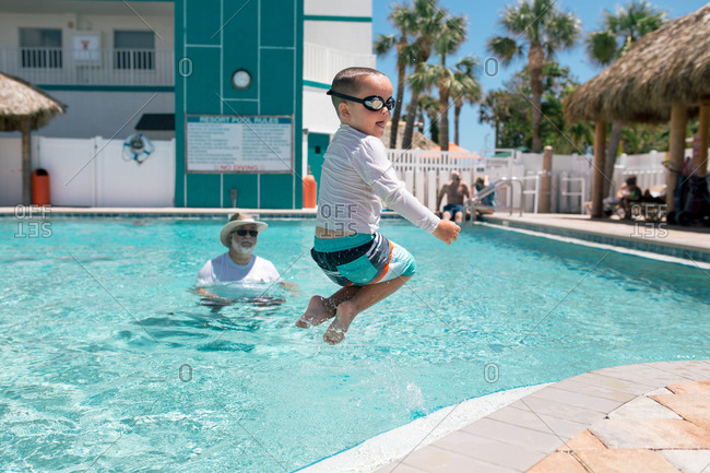 Playful boy jumping into swimming pool