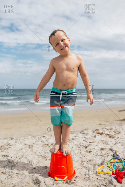 Portrait of playful boy standing on bucket at beach against cloudy sky