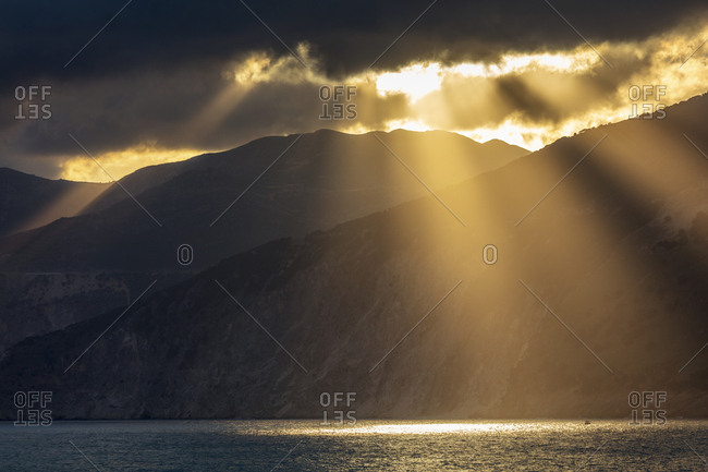 Breathtaking sunbeams between the clouds, mountain and sea