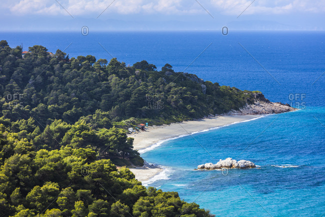 Beach between green forest and azure sea