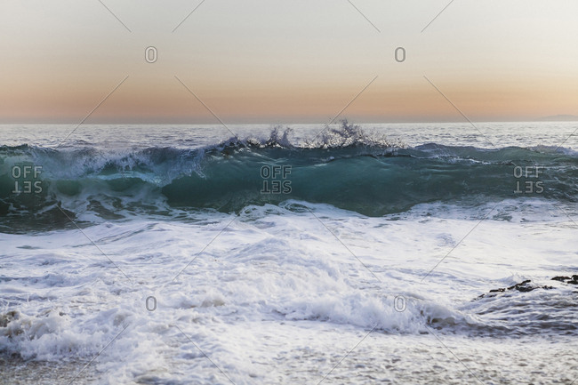 Idyllic view of waves in sea against sky during sunset