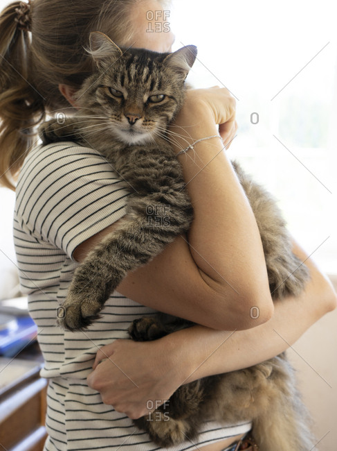 Side view of woman carrying cat while standing at home