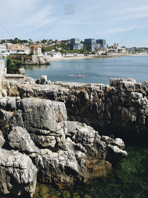 Scenic view of sea with rock formations by city