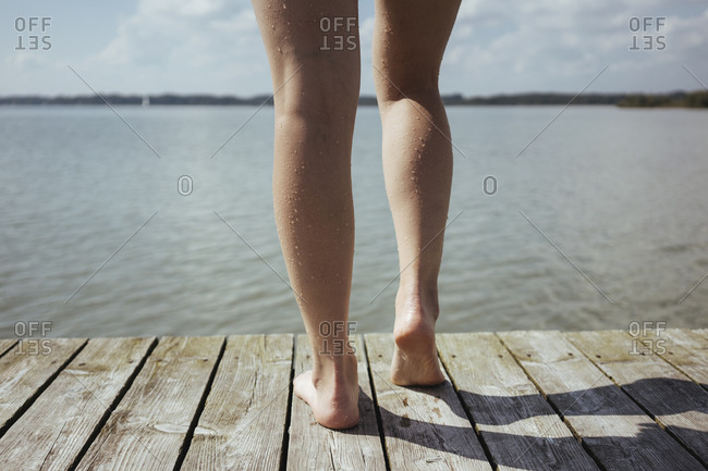 Low section of woman standing on pier over lake against sky during sunny day