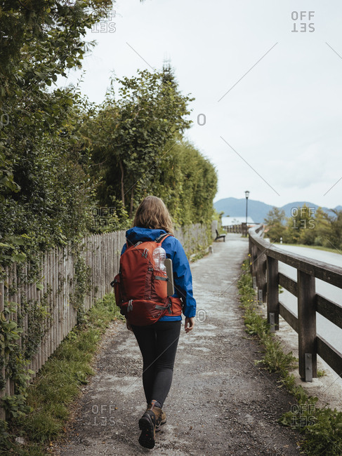 Rear view of female backpacker walking on footpath by plants
