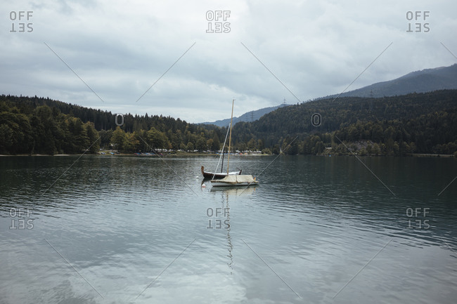 Boats in lake against mountains and cloudy sky