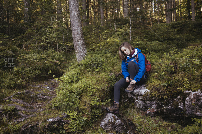 Woman tying shoelace while sitting on rock against trees in forest