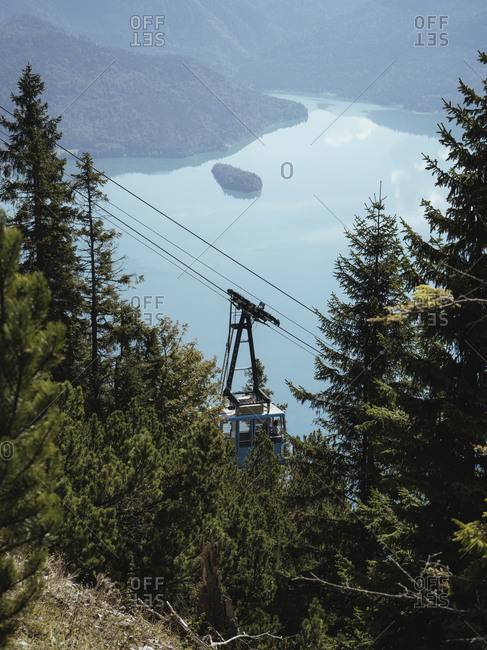 High angle view of overhead cable car moving over lake during sunny day