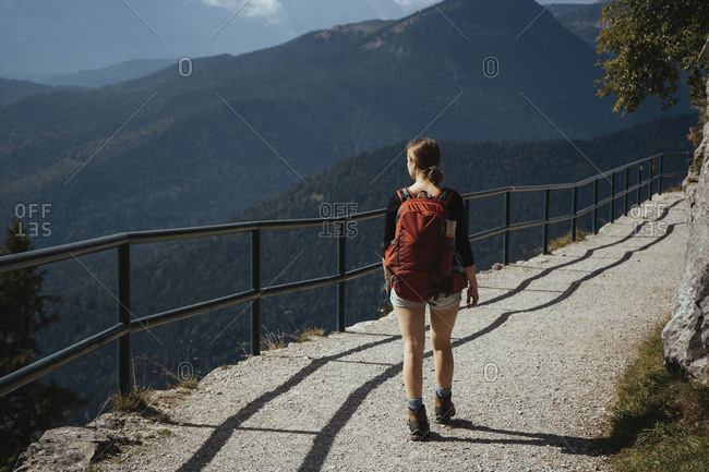 Rear view of female hiker with backpack walking on footpath against mountains during sunny day