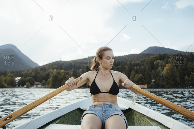 Woman rowing boat on lake against cloudy sky