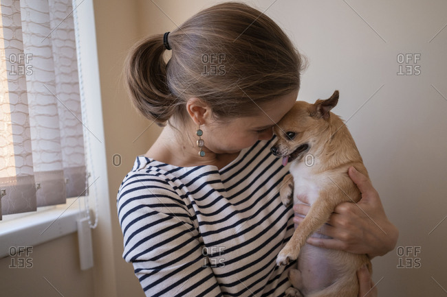 Smiling woman carrying cute Chihuahua while standing against wall at home