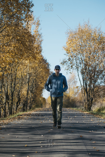 Man with hands in pockets walking on road amidst trees in forest during autumn