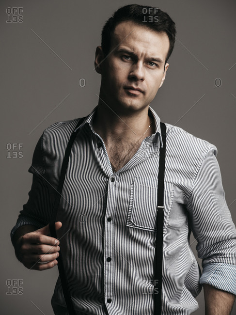 Portrait of handsome businessman wearing suspenders while standing against gray background