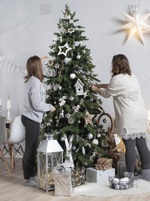Side view of female friends decorating Christmas tree while standing at home