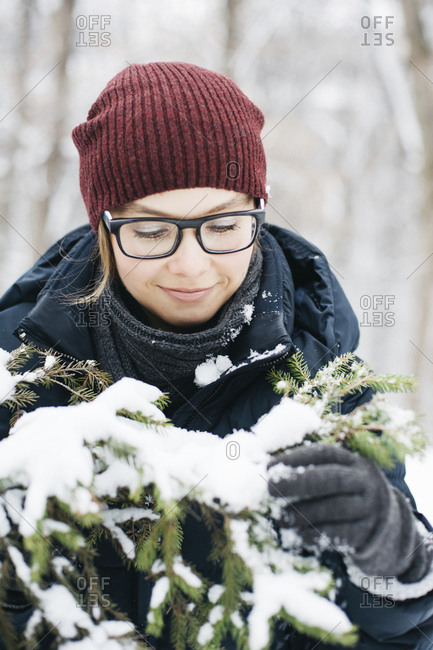 Young woman in glasses enjoying her walk in winter forest