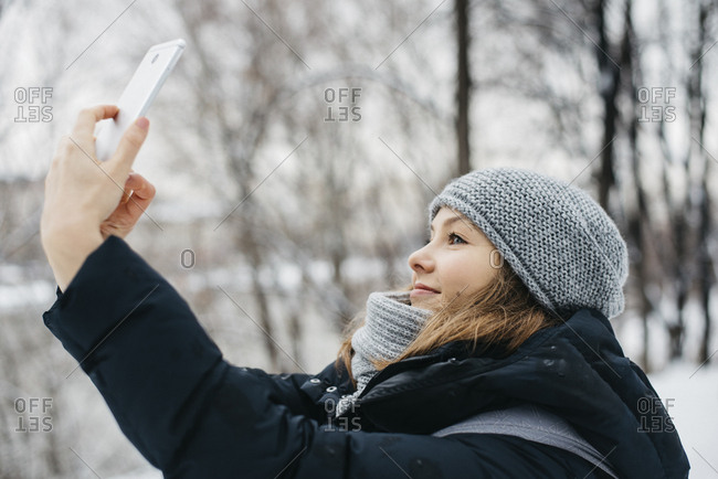 Young woman in hat and scarf with phone getting a selfie